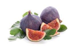 Frutas de la higuera enteras y de la parte con las hojas Foto de archivo libre de regalías