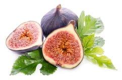 Frutas de la higuera enteras y de la parte con las hojas Fotografía de archivo libre de regalías