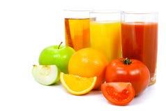 Frutas de la naranja y del tomate de Apple con el jugo en vidrio Foto de archivo libre de regalías