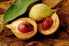 Frutas de la nuez moscada moscada en de madera Imagen de archivo libre de regalías