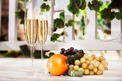 Frutas del otoño y dos vidrios de vino blanco en el backgro ligero Imagenes de archivo