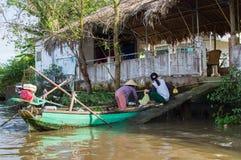 Frutas e legumes vietnamianas do comércio da mulher de um barco de madeira Fotos de Stock Royalty Free