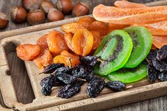 Frutas e porcas secadas Placa velha da cozinha e tabela de madeira imagem de stock royalty free