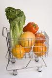 Frutas e verdura frescas em um carro de compra do metal de encontro a um w imagem de stock royalty free
