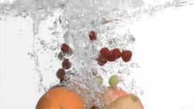 Frutas en la cámara lenta estupenda que baja en el agua almacen de video