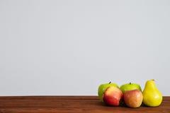 Frutas en la tabla de madera y la pared blanca Foto de archivo