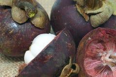 Frutas enteras del mangostán delicioso maduro y cortado en el remiendo del cierre del bolso del cáñamo encima de la foto Fotos de archivo