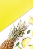 Frutas exóticas cortadas en el espacio amarillo y blanco de la opinión superior del fondo para el texto Foto de archivo libre de regalías