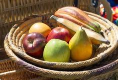 Frutas falsas para la decoración en un cuenco de mimbre Foto de archivo libre de regalías
