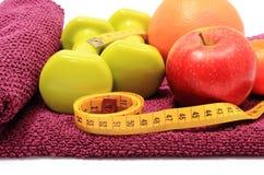 Frutas frescas, cinta métrica y pesas de gimnasia verdes en la toalla púrpura Fotografía de archivo