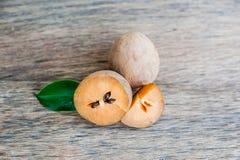 Frutas frescas del zapote en viejo fondo de madera imagen de archivo libre de regalías