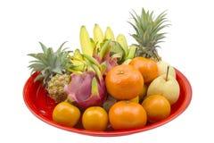 Frutas frescas en la bandeja roja aislada en un blanco Imagenes de archivo