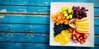 Frutas frescas en la placa blanca en la tabla azul foto de archivo libre de regalías