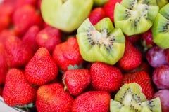 Frutas frescas en la placa Fresas, kiwi, uvas en la tabla de banquete del abastecimiento Foto de archivo