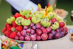 Frutas frescas en la placa Fresas, kiwi, uvas en la tabla de banquete del abastecimiento Imagenes de archivo