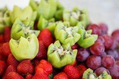 Frutas frescas en la placa Fresas, kiwi, uvas en la tabla de banquete del abastecimiento Imagen de archivo libre de regalías