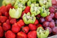 Frutas frescas en la placa Fresas, kiwi, uvas en la tabla de banquete del abastecimiento Fotos de archivo