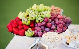 Frutas frescas en la placa Fresas, kiwi, uvas en la tabla de banquete del abastecimiento Foto de archivo libre de regalías