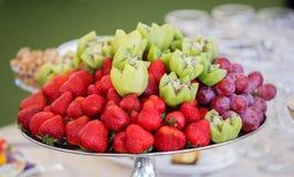 Frutas frescas en la placa Fresas, kiwi, uvas en la tabla de banquete del abastecimiento Fotografía de archivo libre de regalías