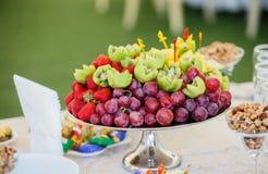 Frutas frescas en la placa Fresas, kiwi, uvas en la tabla de banquete del abastecimiento Imagen de archivo