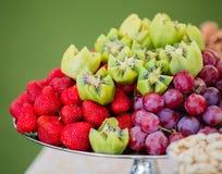 Frutas frescas en la placa Fresas, kiwi, uvas y anacardos en la tabla de banquete del abastecimiento Imagen de archivo libre de regalías