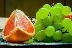 Frutas frescas, pomelo con las uvas en una placa de metal Foto de archivo