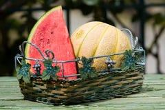 Frutas frescas, sandía y rockmelon estacionales en cesta en la sobremesa, al aire libre Imagen de archivo