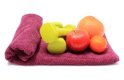 Frutas frescas y pesas de gimnasia verdes en la toalla púrpura Fotos de archivo libres de regalías