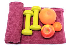 Frutas frescas y pesas de gimnasia verdes en la toalla púrpura Foto de archivo libre de regalías