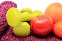 Frutas frescas y pesas de gimnasia verdes en la toalla púrpura Imagen de archivo