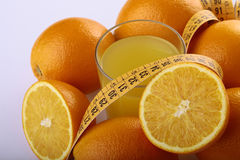 Frutas, jugo y cinta métrica anaranjados Fotos de archivo