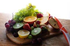Frutas jugosas con el cuchillo en un tablero de madera Imagen de archivo
