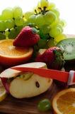 Frutas jugosas con el cuchillo en un tablero de madera Foto de archivo libre de regalías