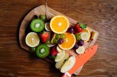 Frutas jugosas con el cuchillo en un tablero de madera Fotografía de archivo