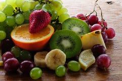 Frutas jugosas en un tablero de madera Fotografía de archivo