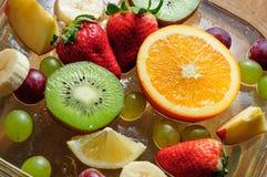 Frutas jugosas en una placa con hielo Fotografía de archivo