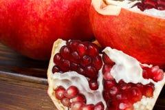 Frutas jugosas rojas de la granada, enteras, medias, maduras y quebradas Imagen de archivo