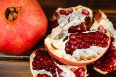 Frutas jugosas rojas de la granada, enteras, medias, maduras y quebradas Fotografía de archivo libre de regalías