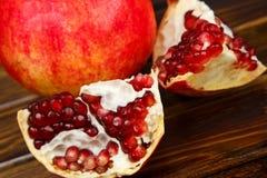 Frutas jugosas rojas de la granada, enteras, medias, maduras y quebradas Imagen de archivo libre de regalías