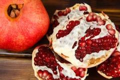 Frutas jugosas rojas de la granada, enteras, medias, maduras y quebradas Fotografía de archivo