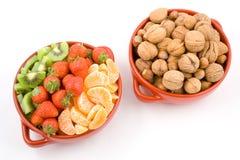 Frutas, kiwi, fresa, mandarín y tuercas, dos tazones de fuente. imagenes de archivo