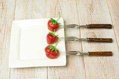 Frutas maduras de la fresa en una placa blanca Imágenes de archivo libres de regalías