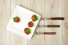 Frutas maduras de la fresa en una placa blanca Imagenes de archivo
