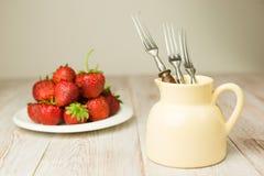 Frutas maduras de la fresa en una placa blanca Imagen de archivo libre de regalías