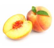 Frutas maduras do pêssego com as folhas verdes isoladas fotografia de stock