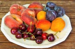 Frutas, melocotones del ciruelo de los albaricoques y cerezas en una placa blanca Foto de archivo