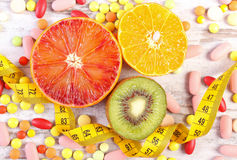 Frutas naturales, centímetro y píldoras médicas, el adelgazar, opción entre la nutrición sana y los suplementos médicos foto de archivo