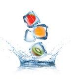 Frutas nos cubos de gelo que espirram na água Foto de Stock Royalty Free