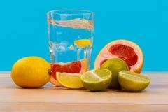Frutas para una dieta sana con un vidrio de agua en un fondo azul Fotografía de archivo