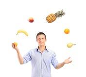Frutas que hacen juegos malabares sonrientes del hombre hermoso imagen de archivo